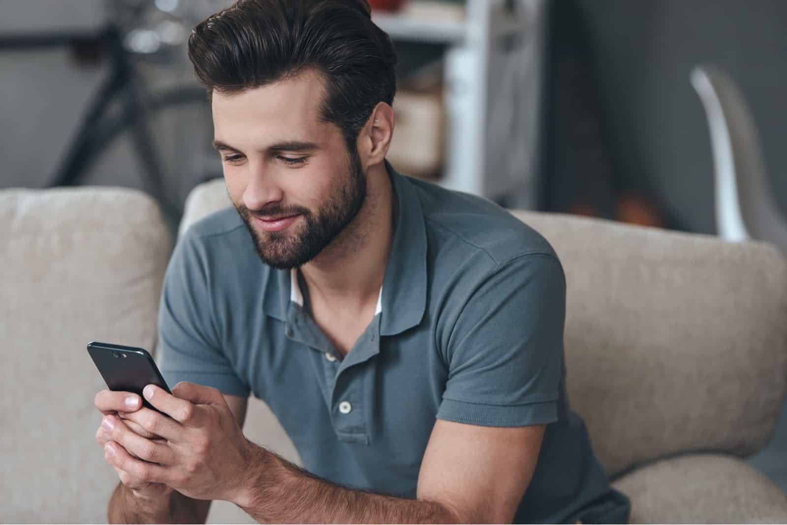 un homme souriant est assis sur le canapé et les touches du téléphone