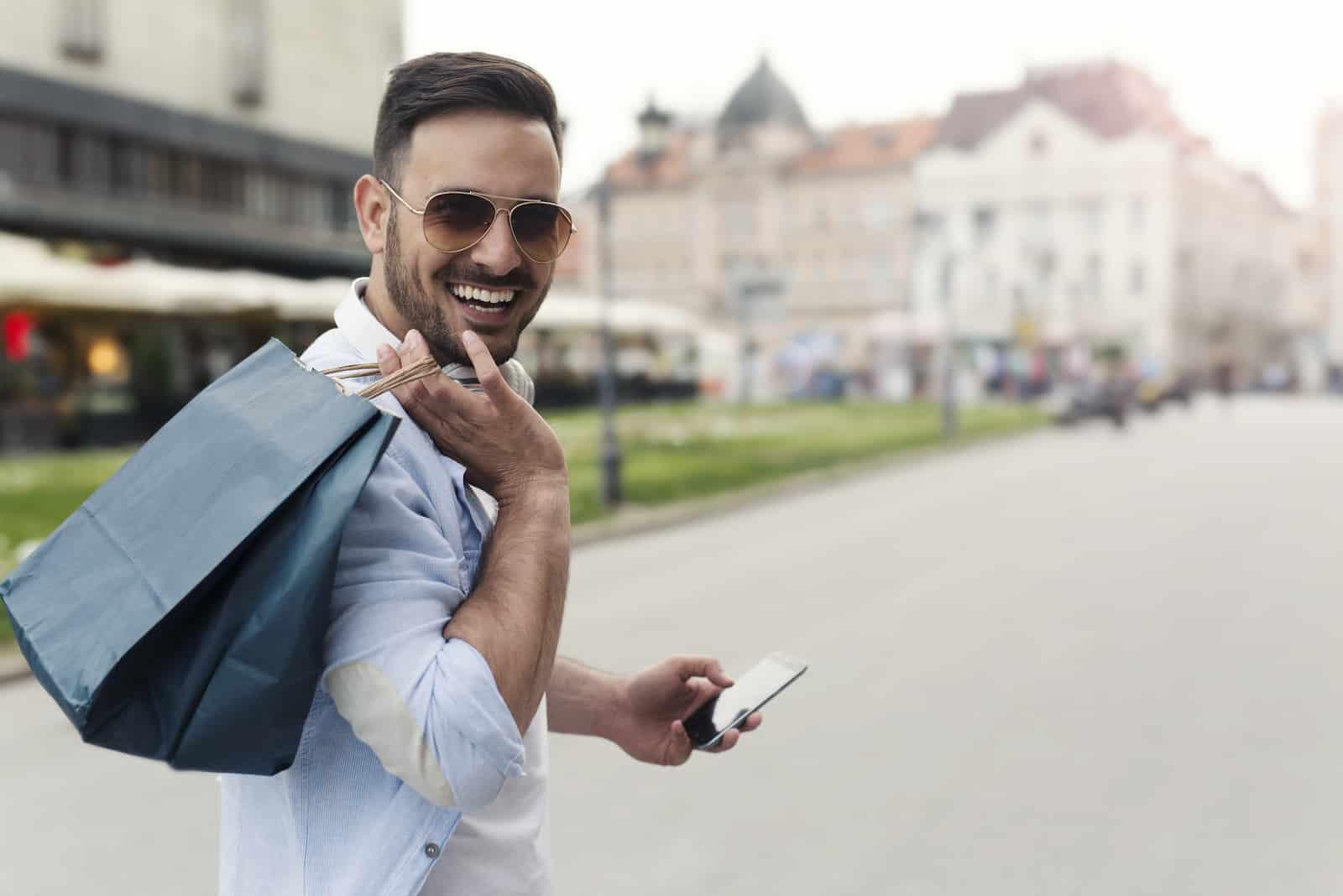 un homme souriant tenant un sac
