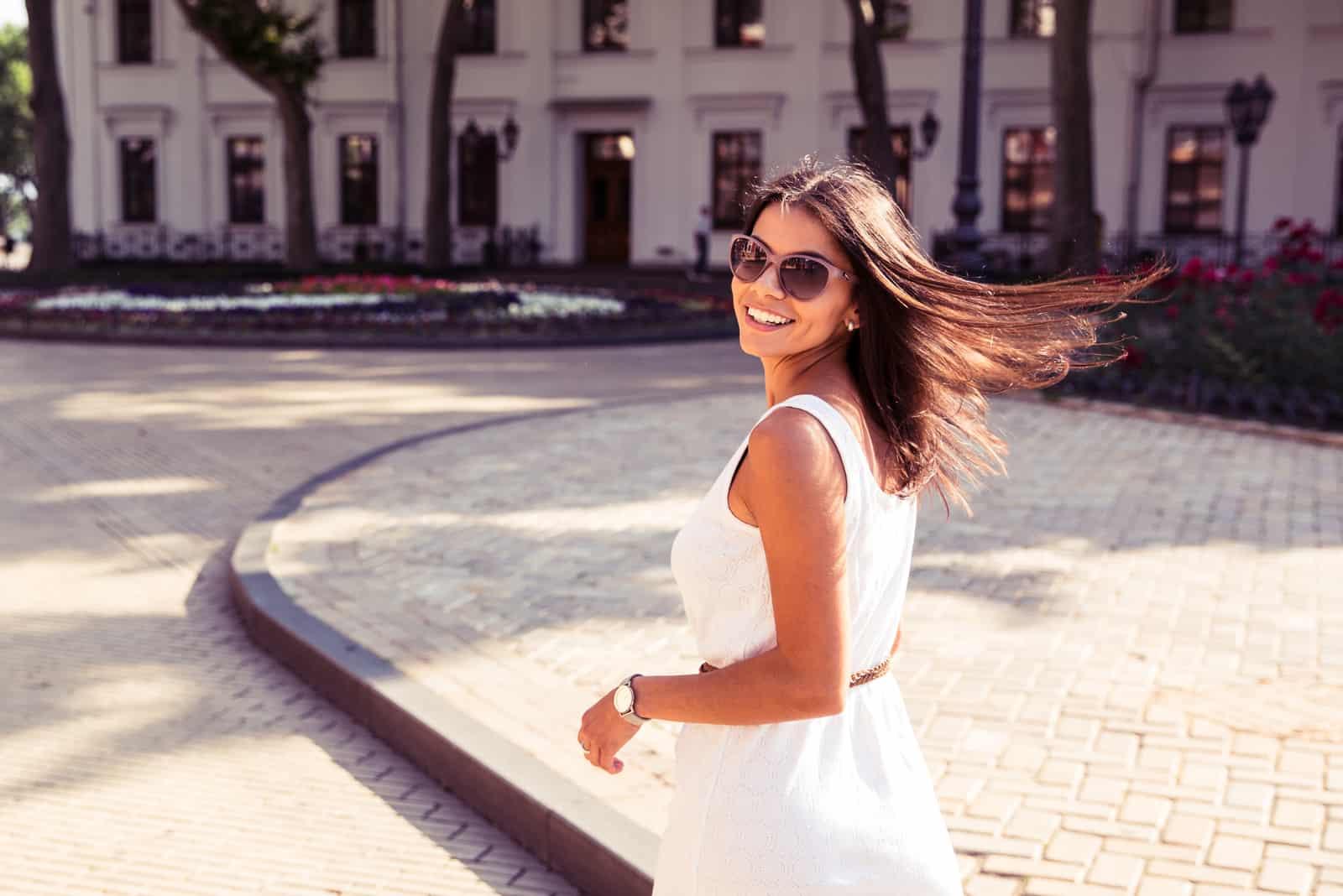 une belle femme aux longs cheveux bruns vêtue d'une robe blanche marche dans la rue