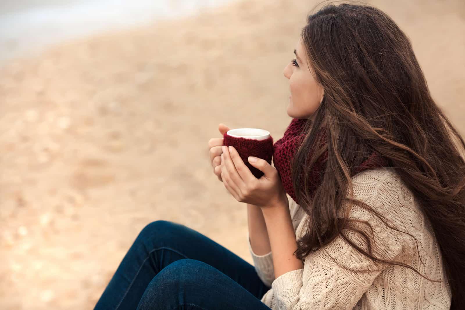 une belle femme aux longs cheveux noirs est assise et tient une tasse de café à la main