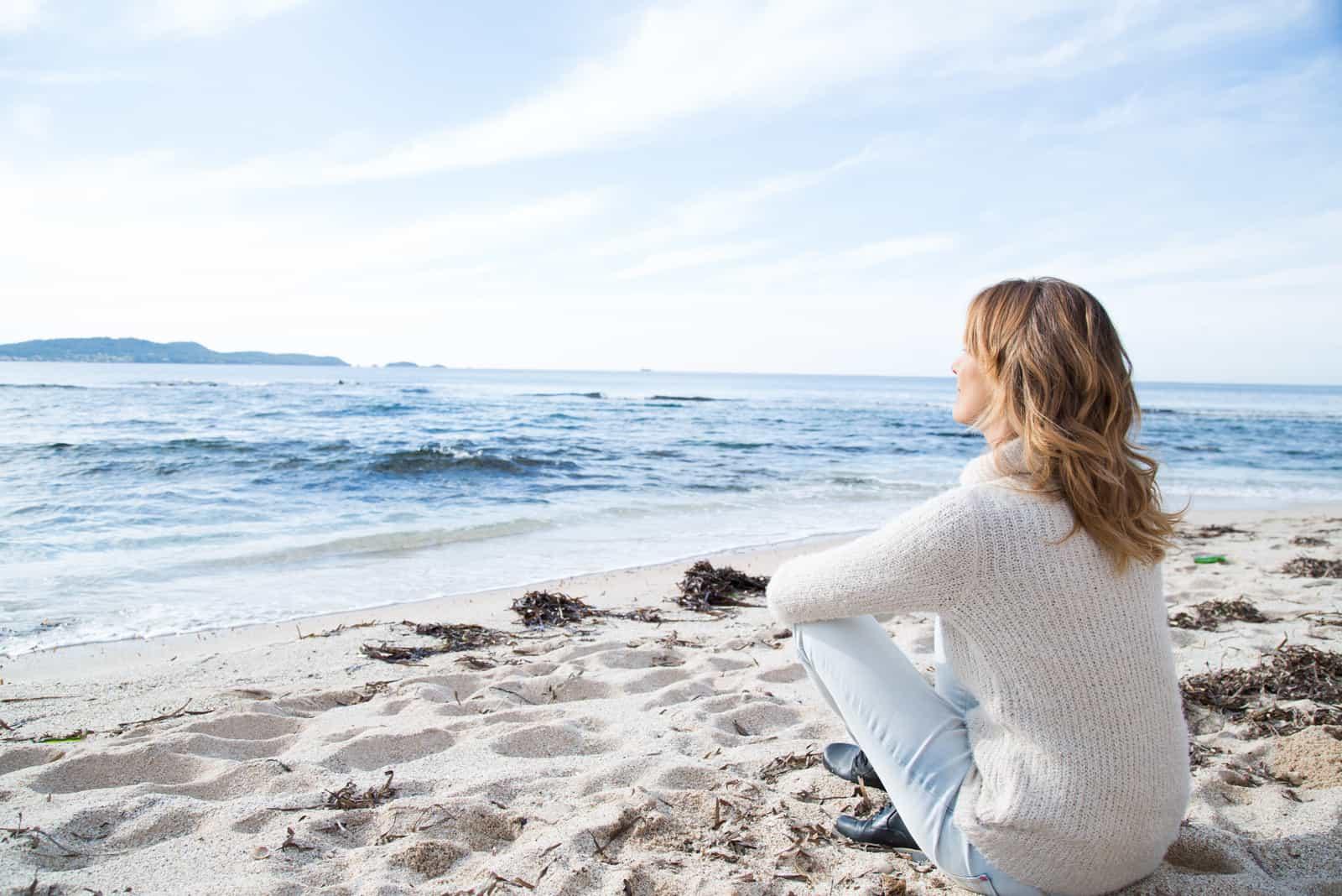 une femme aux longs cheveux bruns est assise sur la plage