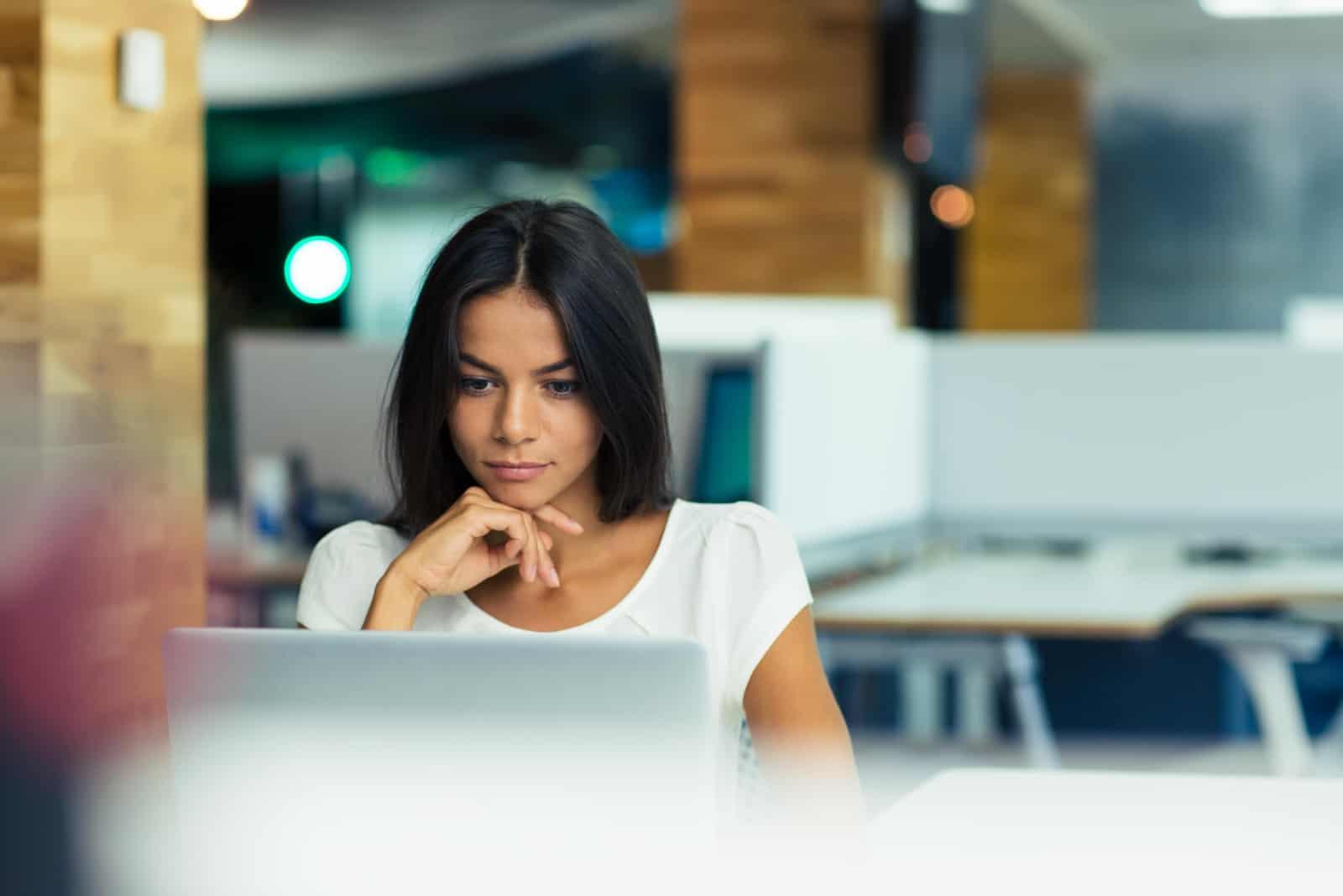 une femme imaginaire assise derrière un ordinateur portable