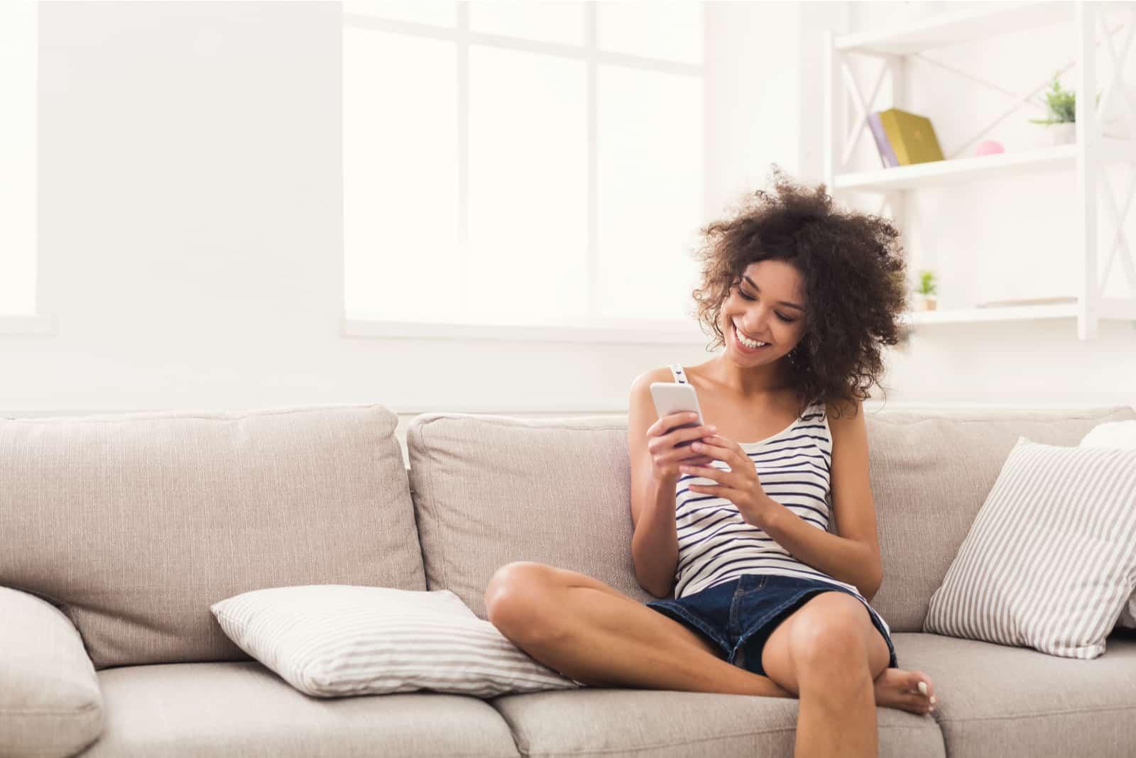 une femme souriante aux cheveux crépus est assise sur le canapé et tape au téléphone