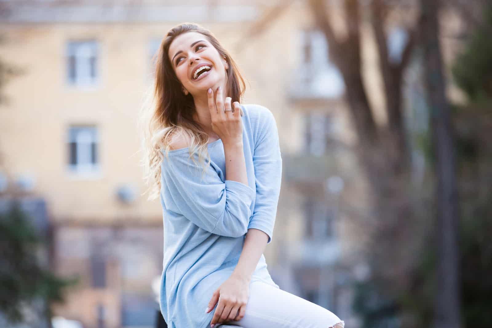 une femme souriante est assise sur la clôture et rit