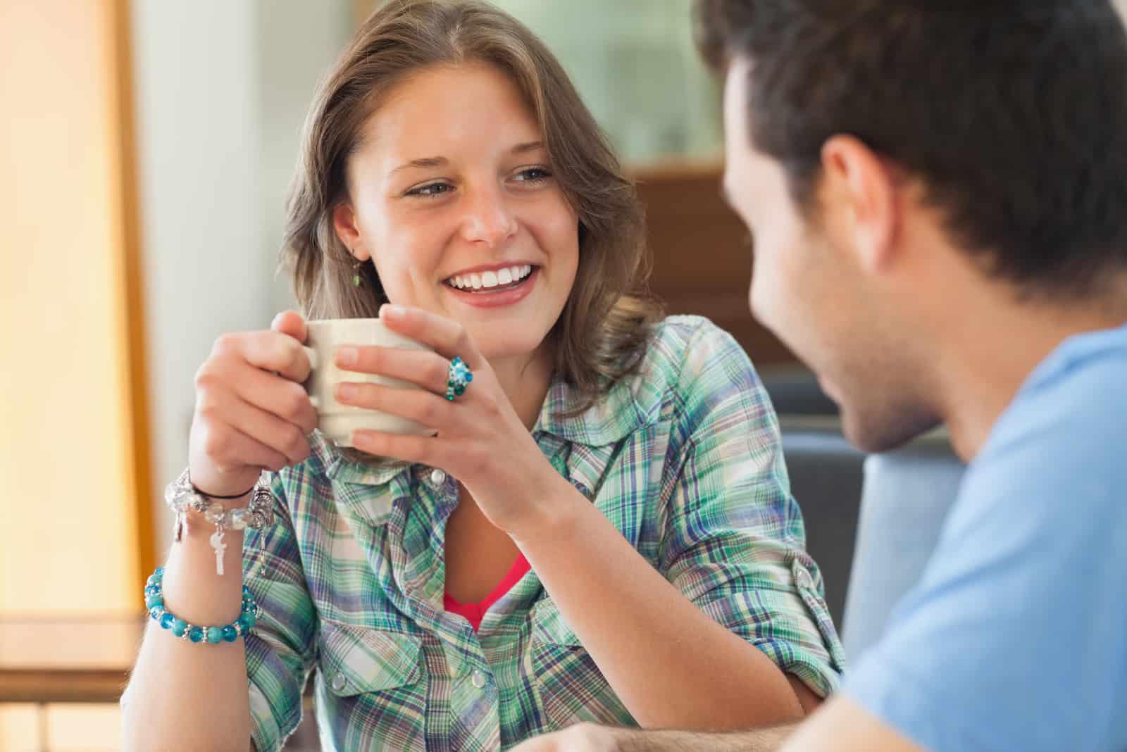 une femme souriante parlant à un homme autour d'un café