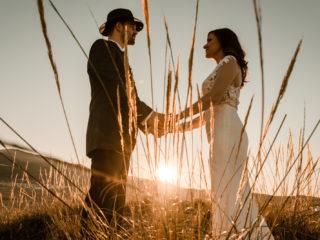 un homme et une femme se tenant la main dans un champ de blé