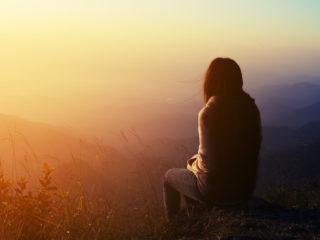 une femme triste est assise sur un rocher et regarde devant elle