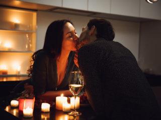 un homme et une femme sont assis à une table et s'embrassent