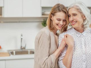 maman souriante et sa fille debout dans la cuisine