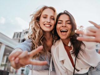 deux femmes prennent des photos et rient