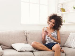 une femme souriante aux cheveux crépus est assise sur le canapé et les touches du téléphone