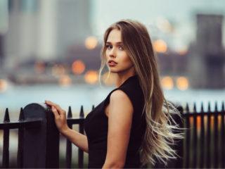 une femme aux longs cheveux bruns se tient appuyée contre une balustrade