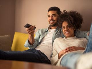 un couple d'amoureux souriant allongé sur le canapé et regardant la télévision