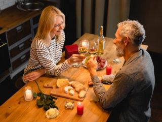 un homme et une femme souriants trinquent avec du vin pendant le dîner