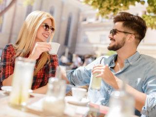 un homme souriant et une femme assise à l'extérieur prenant un café en train de parler