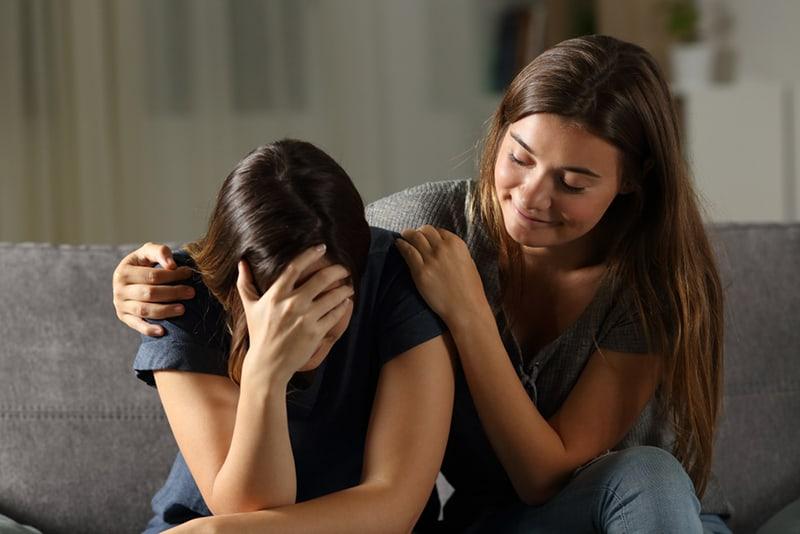 Mauvais ami hypocrite réconfortant une fille triste assise sur un canapé