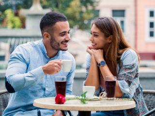 un beau jeune couple assis à l'extérieur et parlant autour d'un café