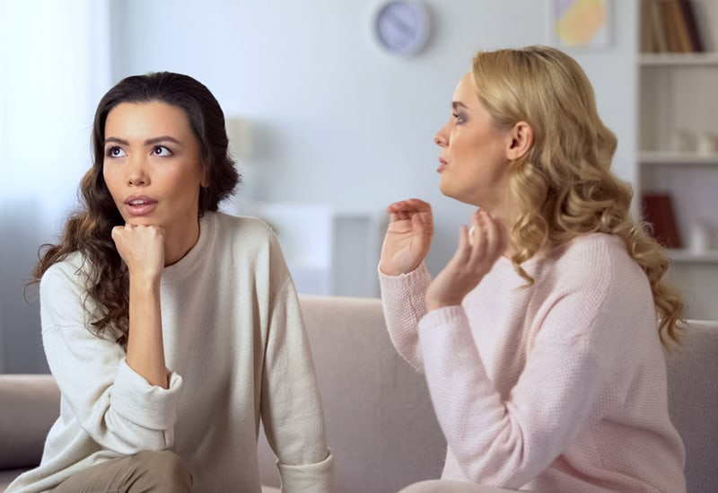 dame s'ennuyant à propos de la conversation avec son amie alors qu'elle était assise sur le canapé ensemble