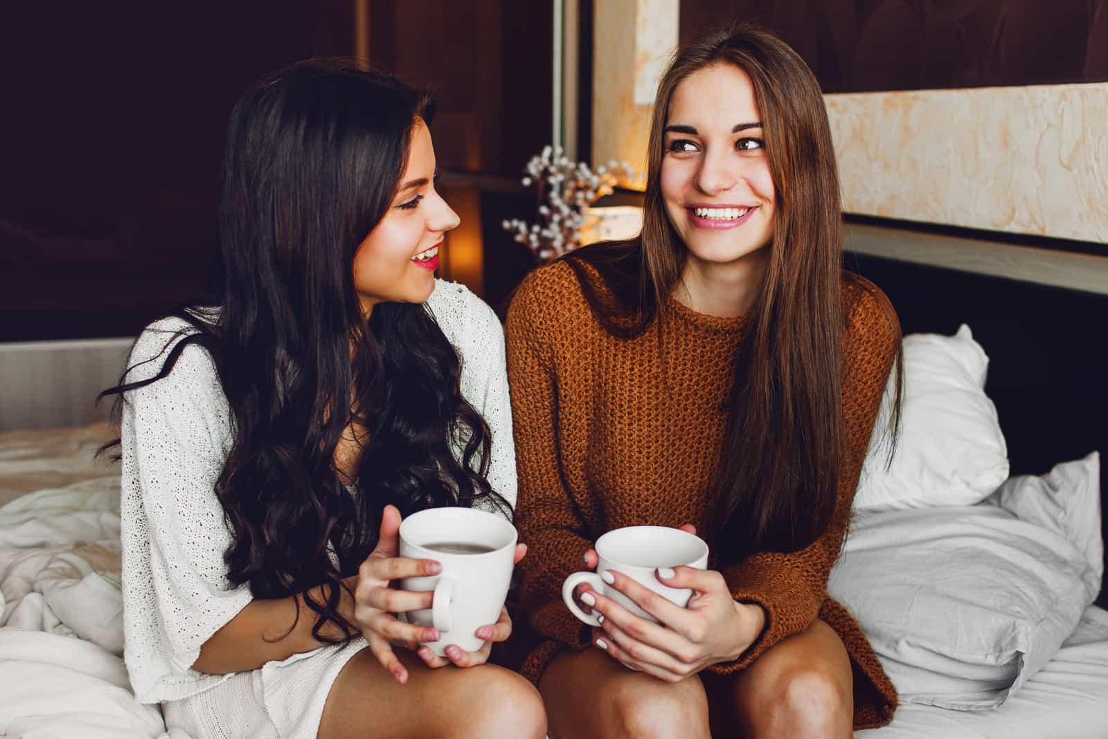 deux amis s'assoient sur le lit et boivent du thé