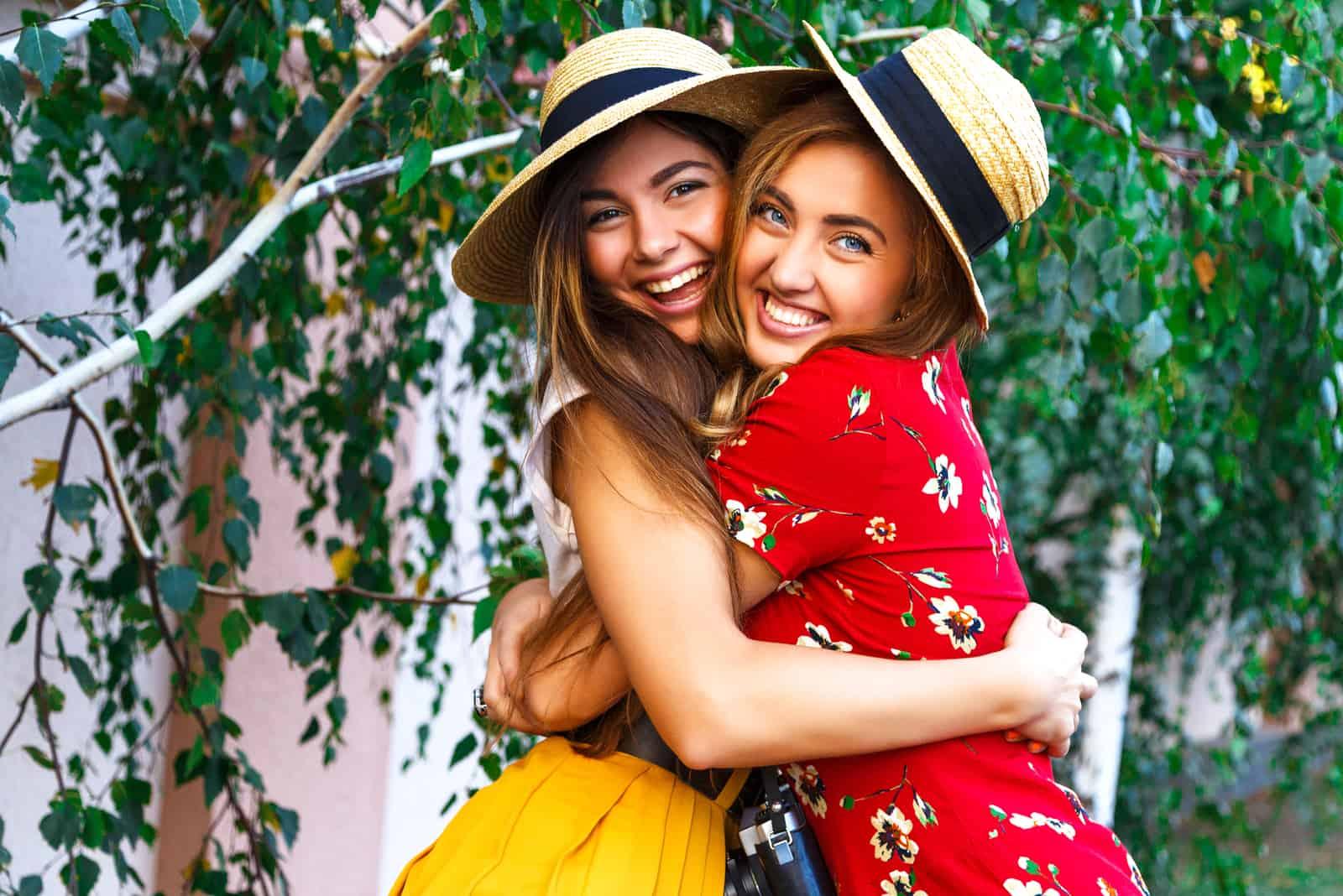 deux femmes avec un chapeau sur la tête embrassées