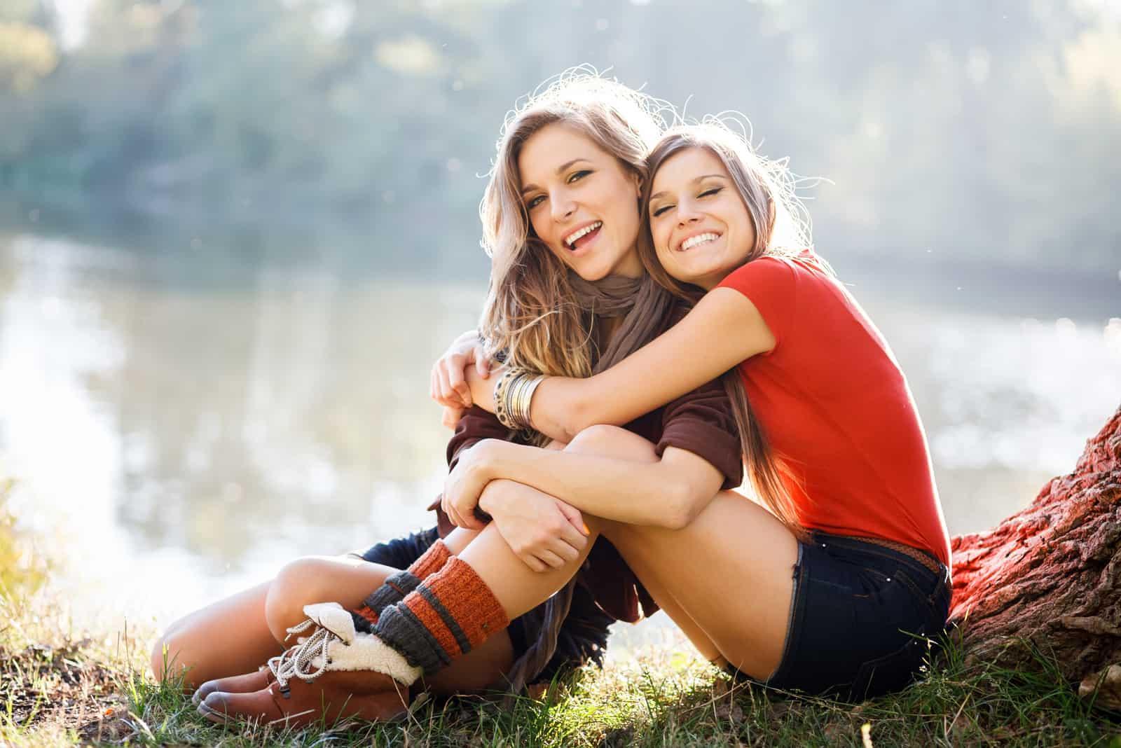 deux femmes embrassant assis sur l'herbe