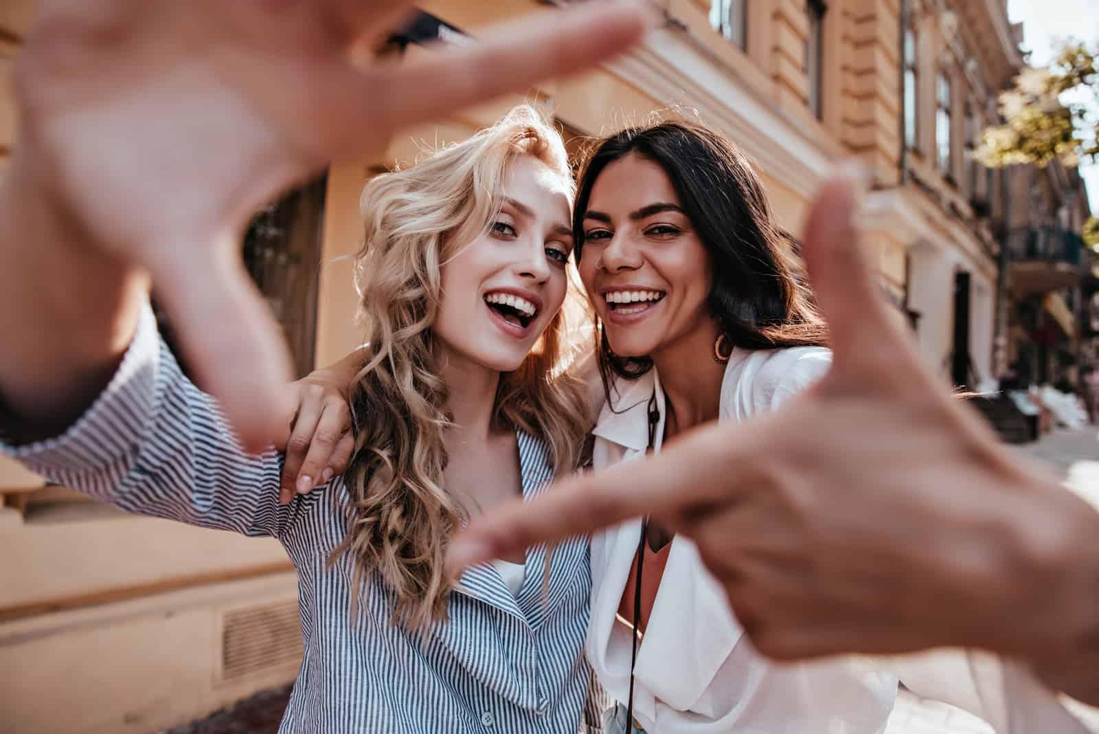 deux femmes souriantes prennent des photos