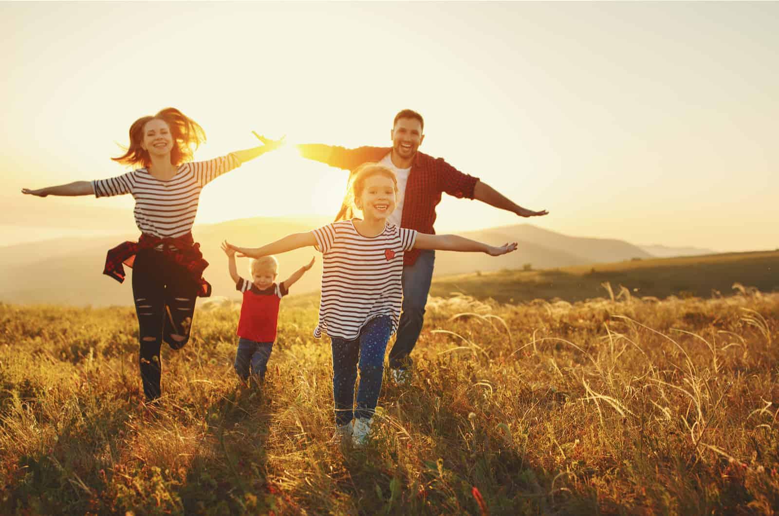 famille heureuse qui traverse le champ
