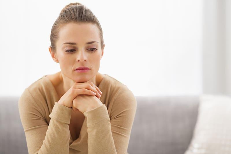 femme réfléchie assise sur le canapé et regardant vers le bas