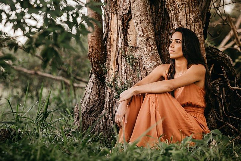 femme réfléchie assise sur l'herbe près de l'arbre
