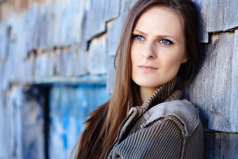 femme réfléchie aux yeux bleus appuyée sur le mur