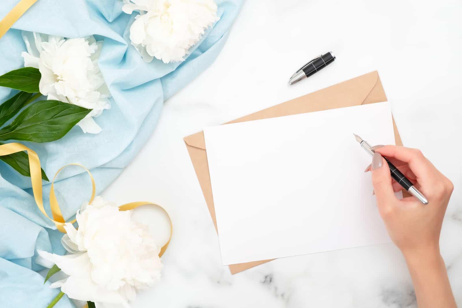 la femme écrit une carte de voeux et emballe des cadeaux