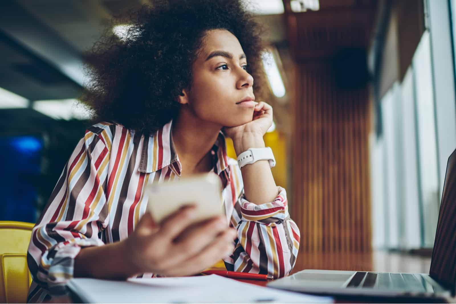 la femme imaginaire est assise et tient le téléphone en détournant les yeux
