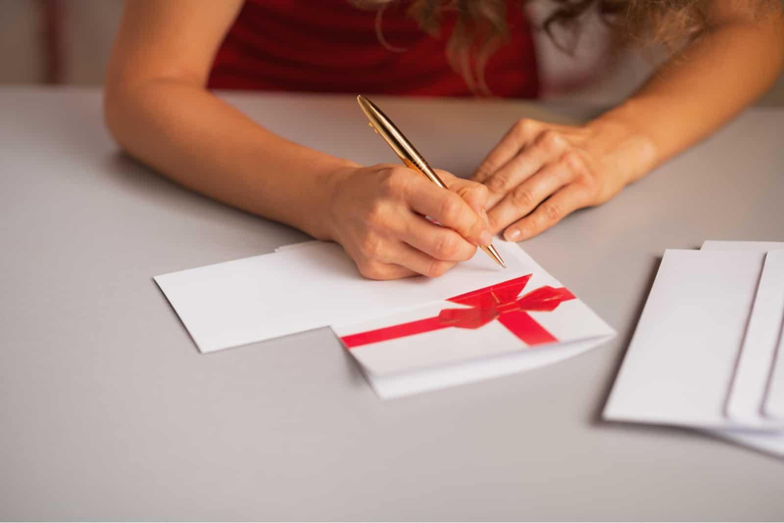 la femme s'assied à la table et écrit une carte de voeux