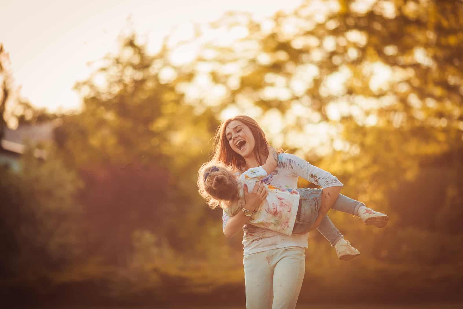 la mère porte sa fille dans ses bras et rit