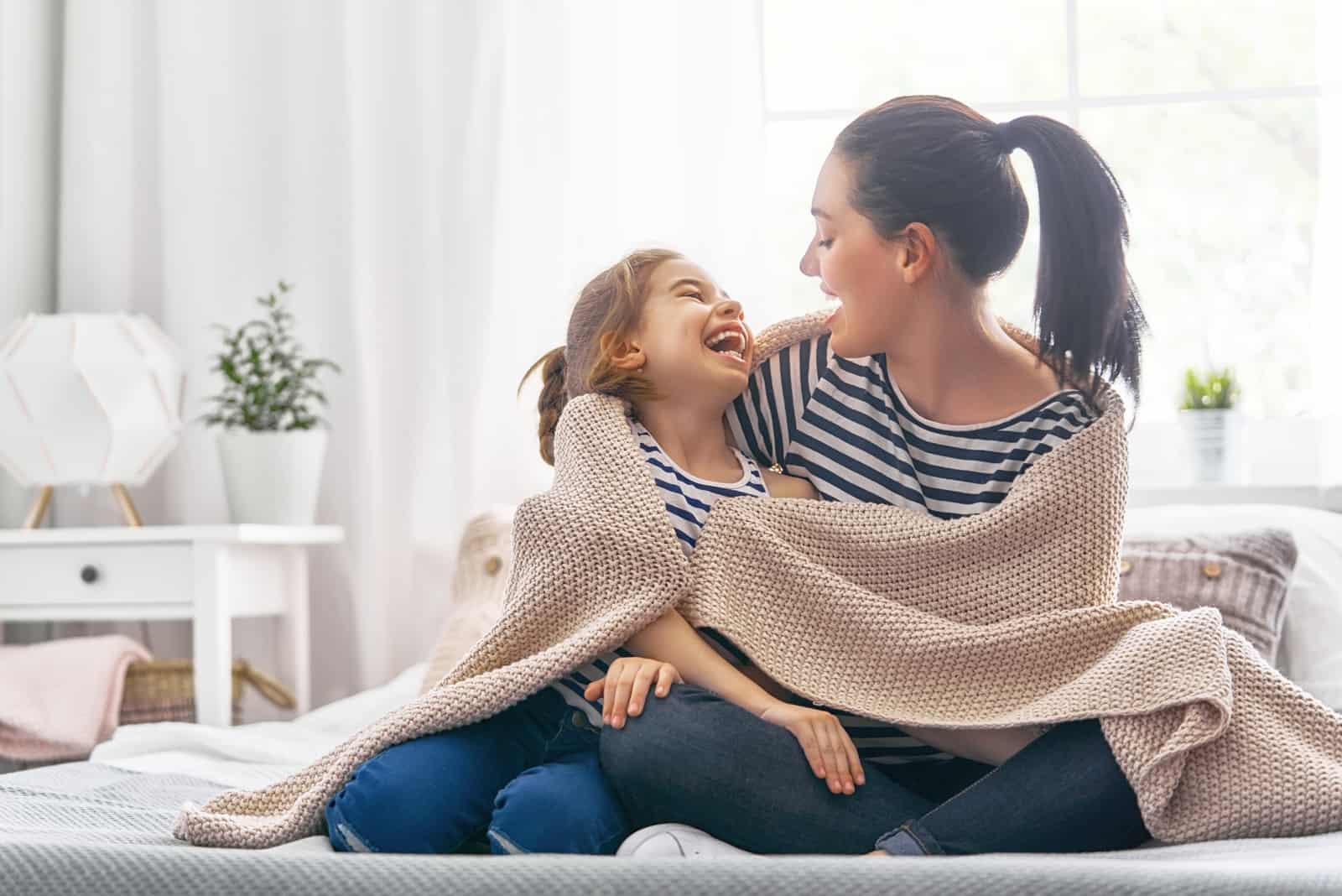 mère et fille embrassées recouvertes d'une couverture