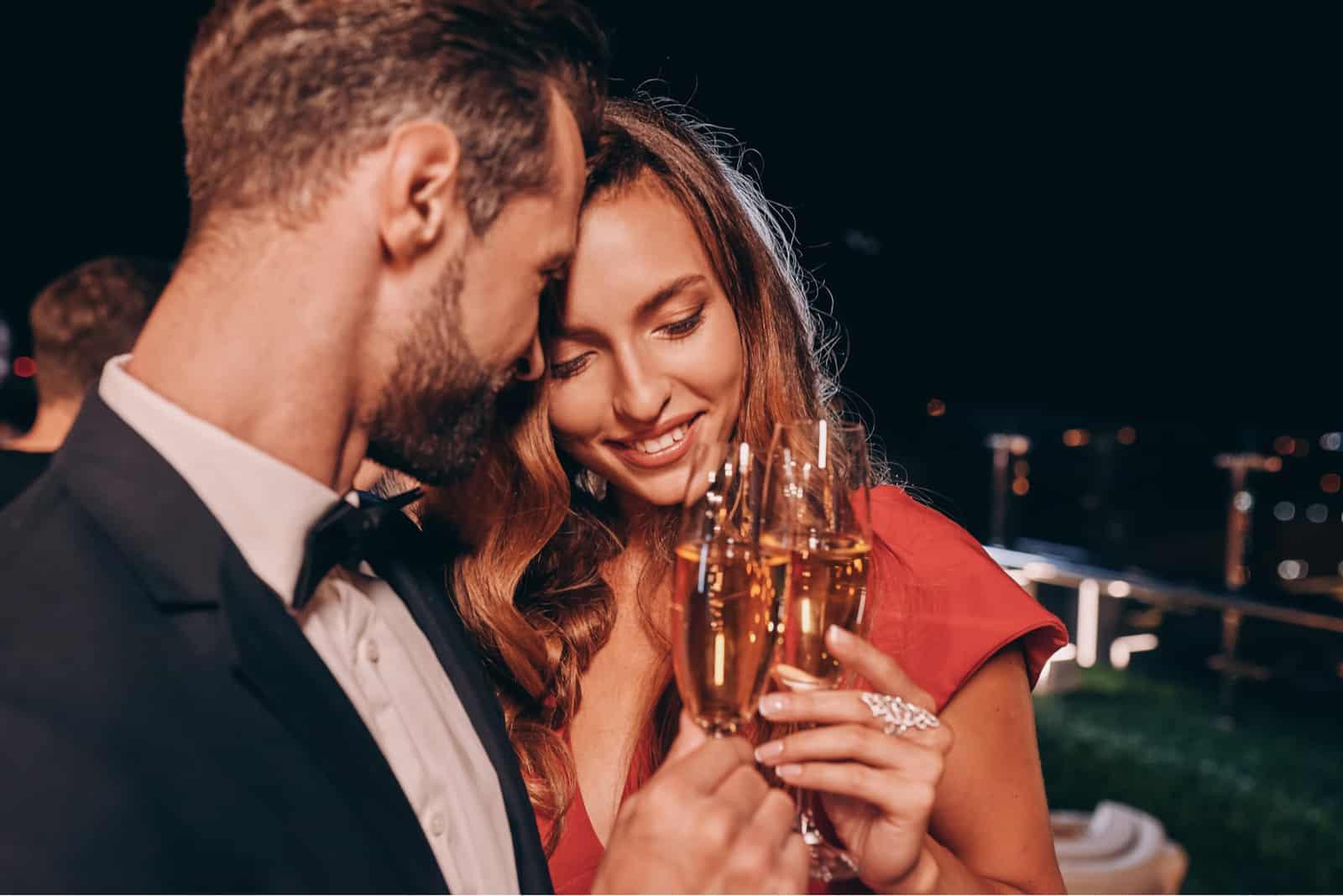 un beau couple debout embrassé le grillage avec du vin