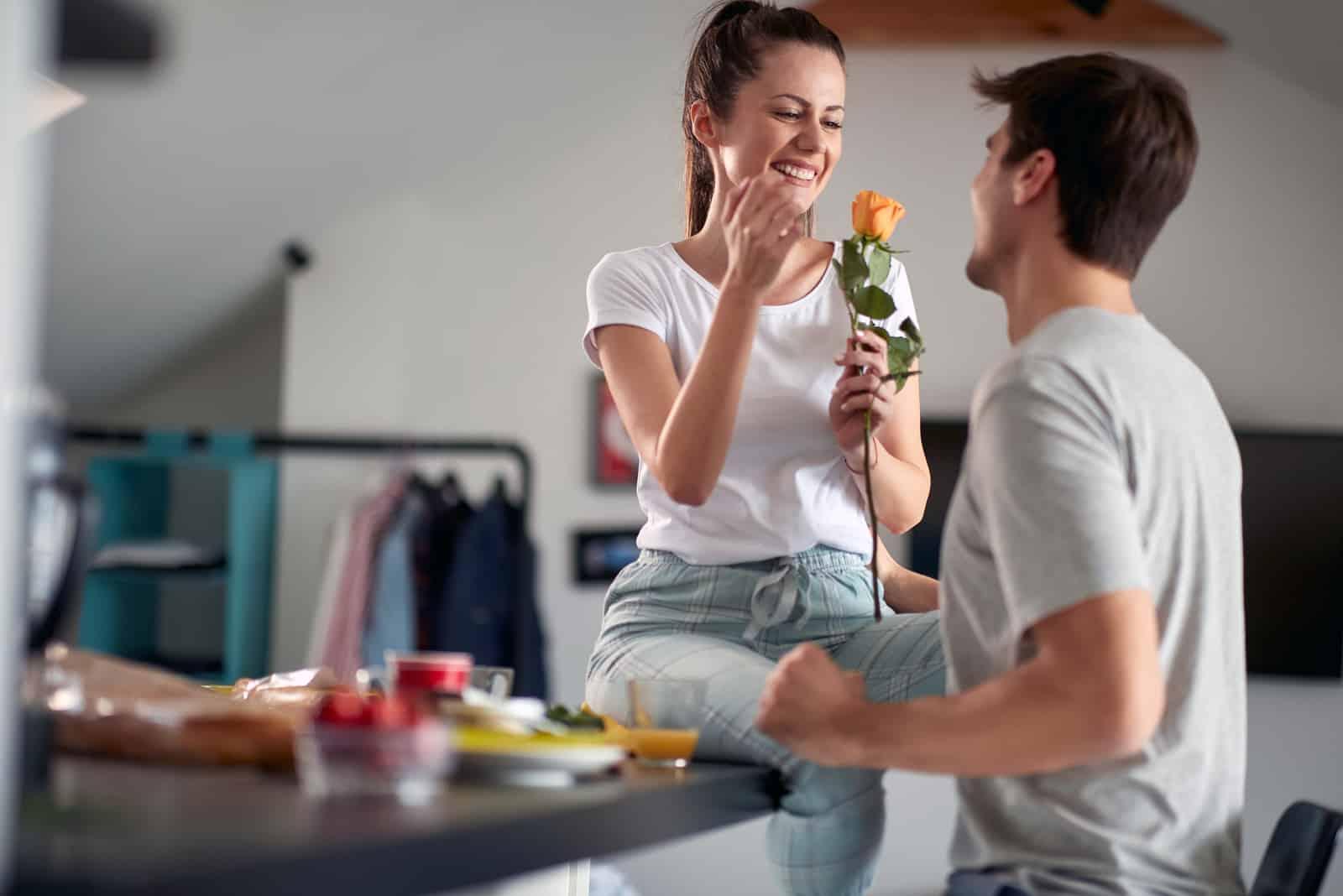 un homme a surpris une femme avec des roses alors qu'elle était assise à une table dans la cuisine
