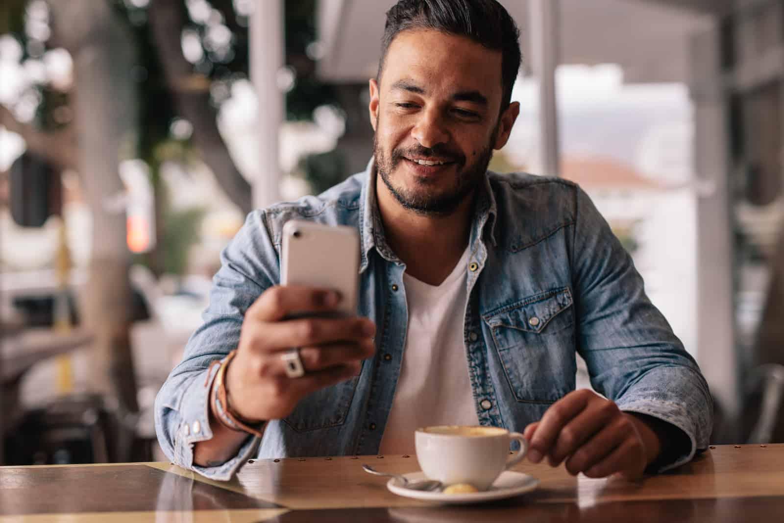 un homme avec des lunettes est assis à une table et un bouton du téléphone