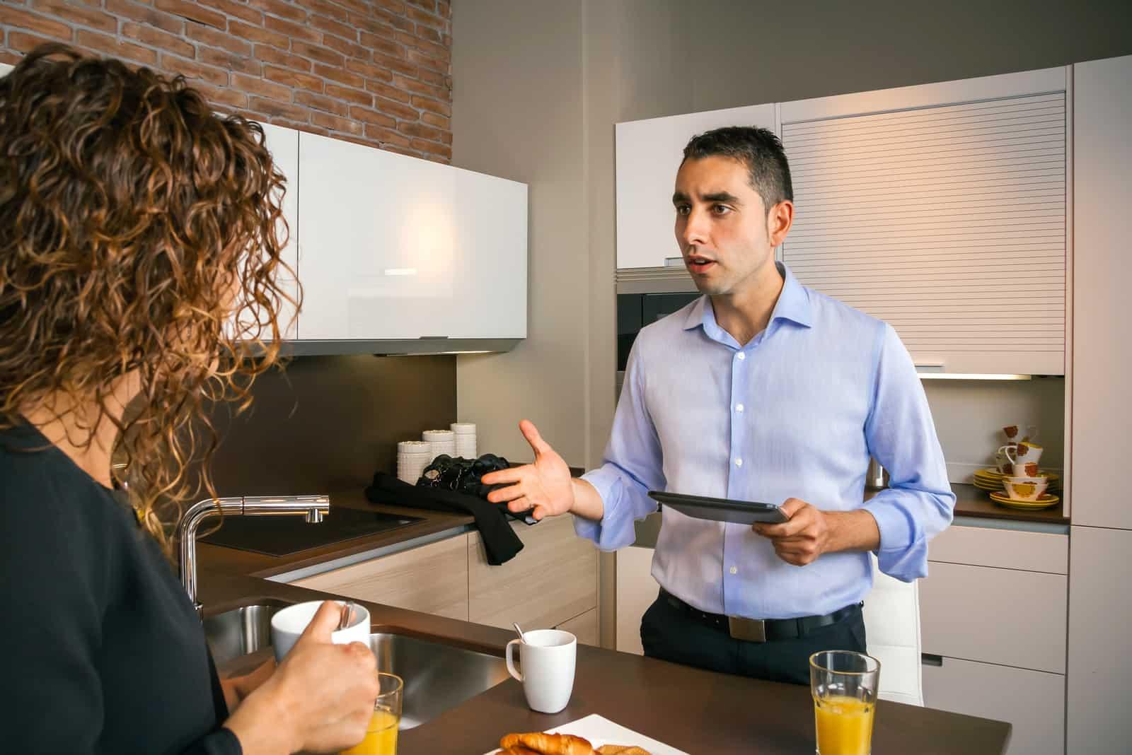 un homme crie après une femme dans la cuisine