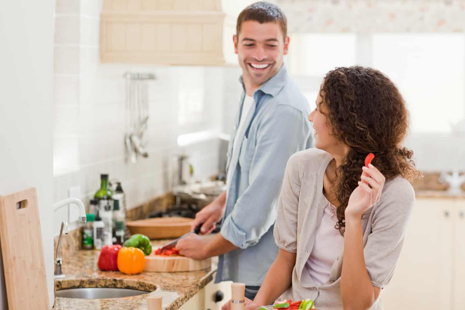 un homme cuisine tandis qu'une femme se tient dans la cuisine