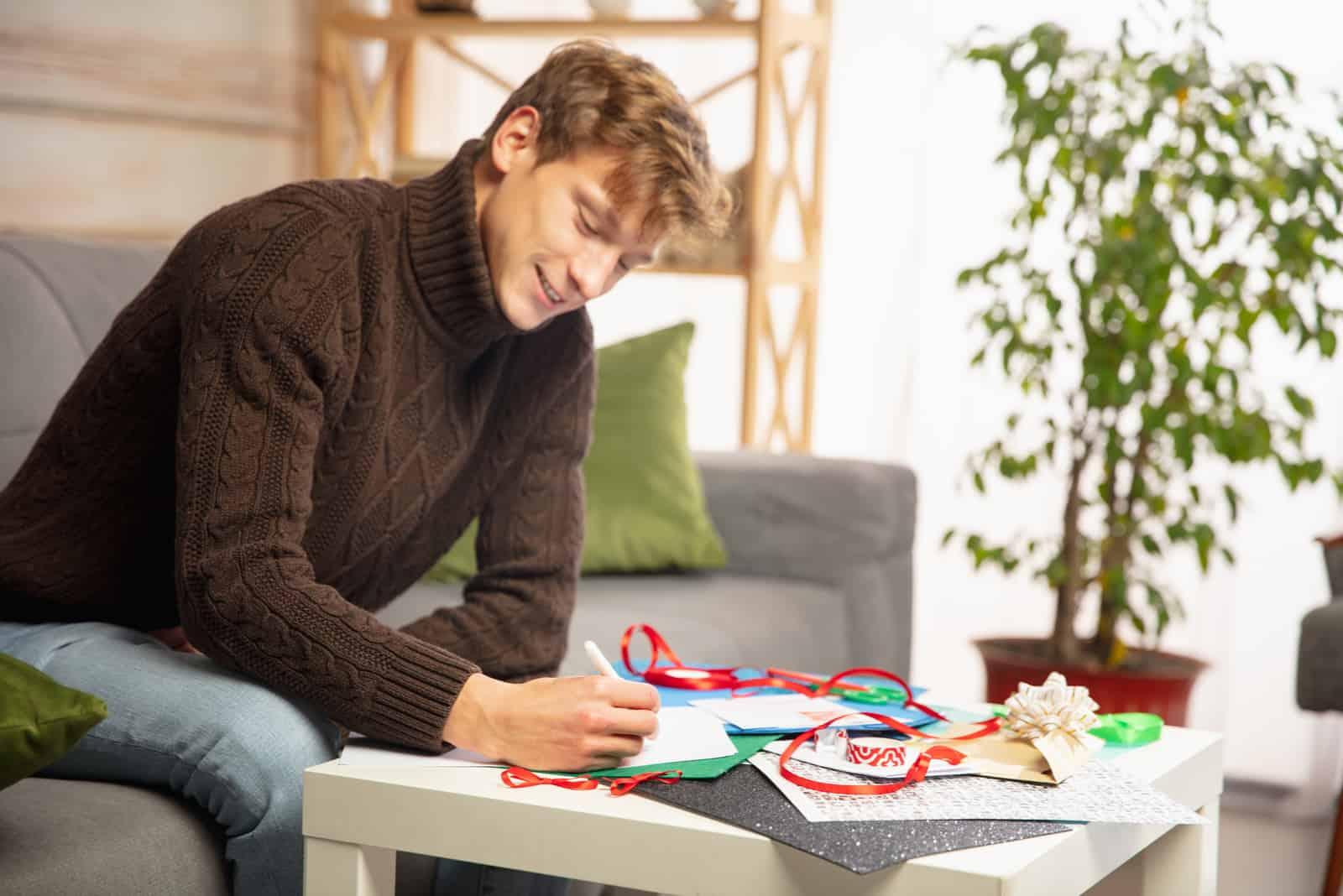 un homme est assis à une table et écrit une carte de voeux