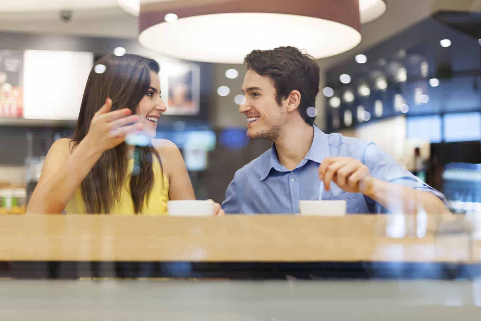 un homme et une femme sont assis dans un café et parlent