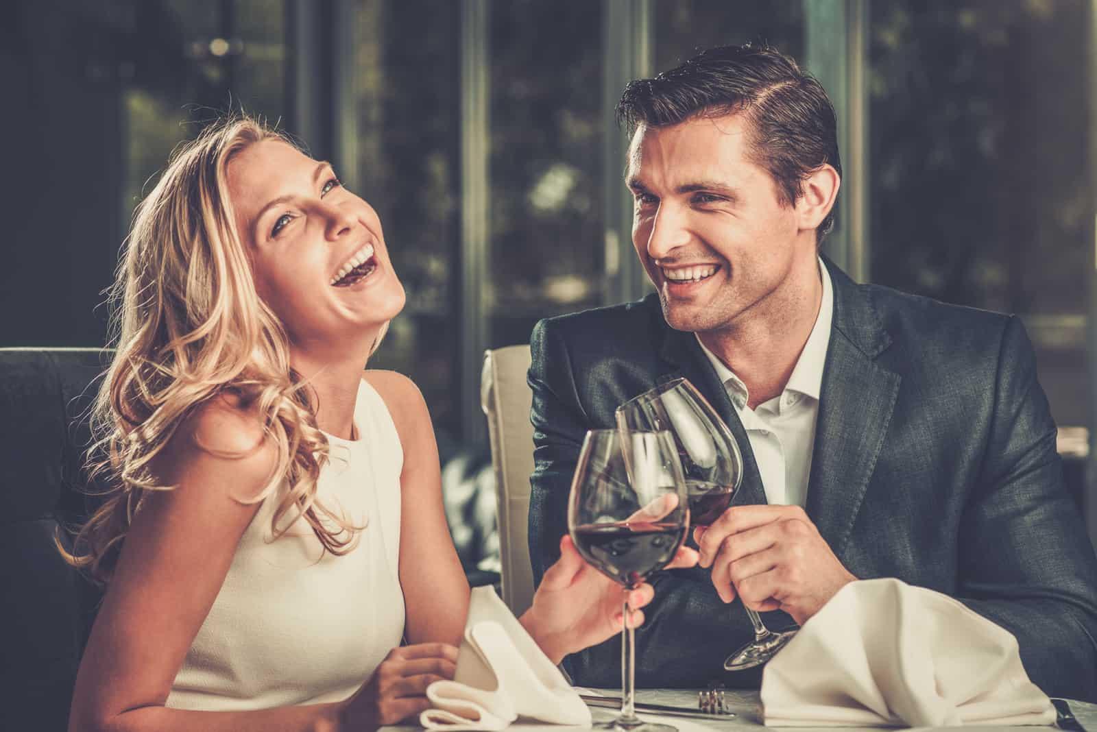 un homme et une femme souriants s'assoient et boivent du vin