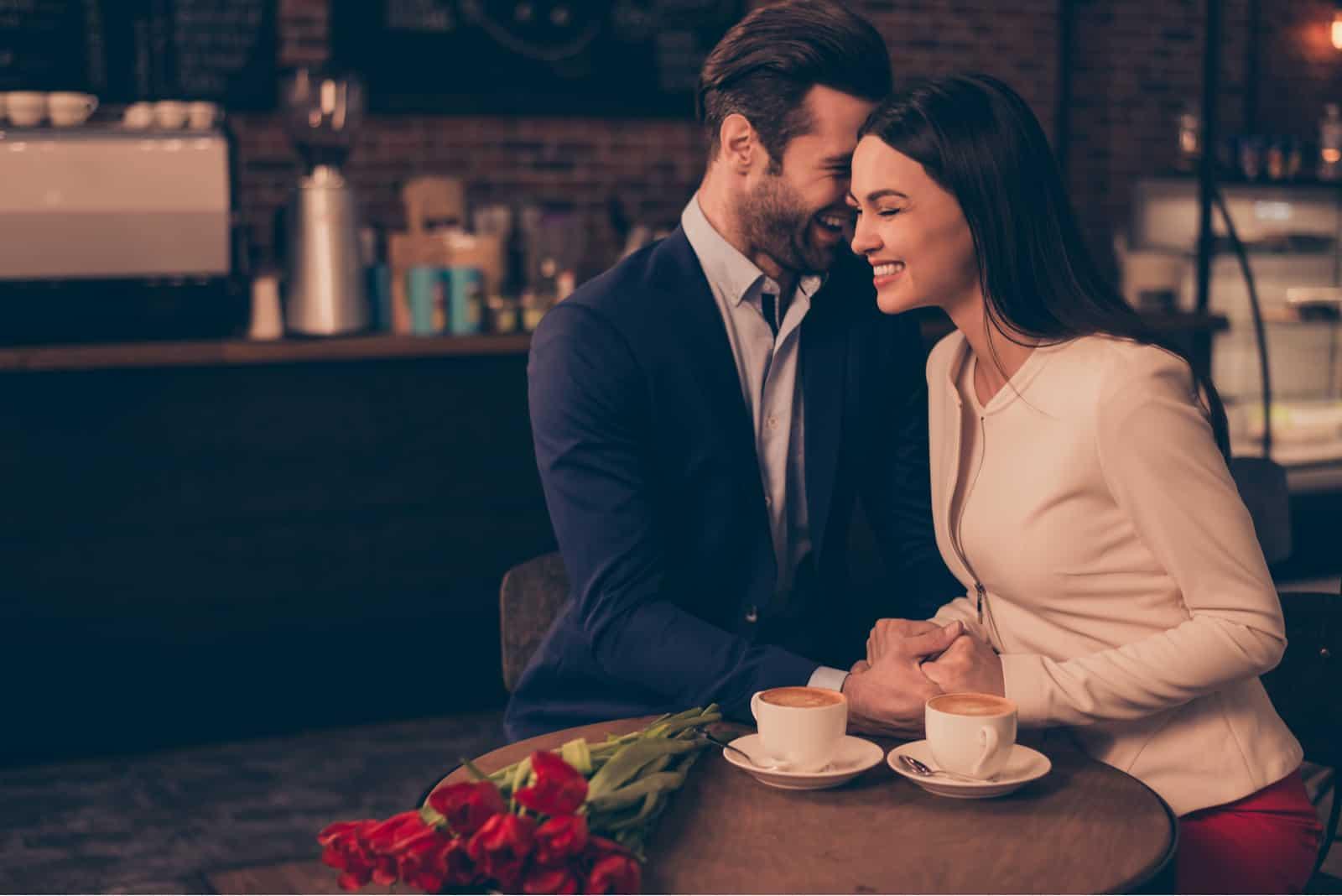 un homme souriant a serré la femme dans ses bras et lui a chuchoté à l'oreille