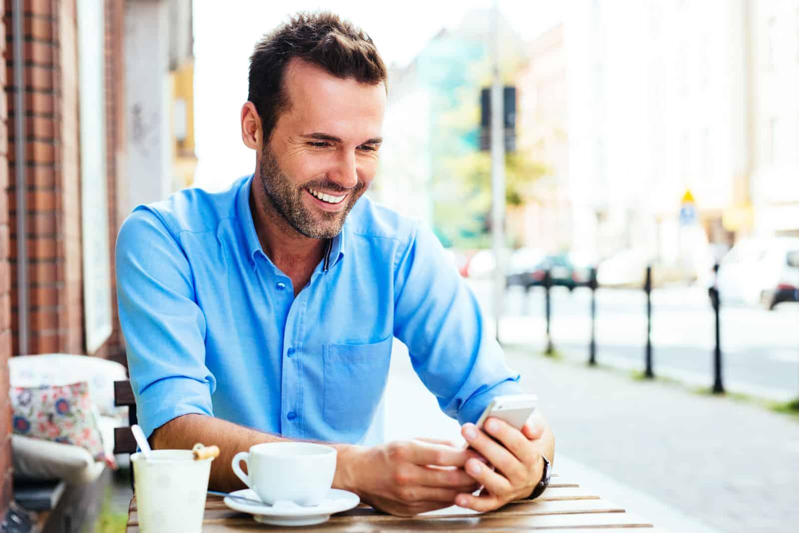 un homme souriant assis à une table en plein air et appuyant sur un téléphone