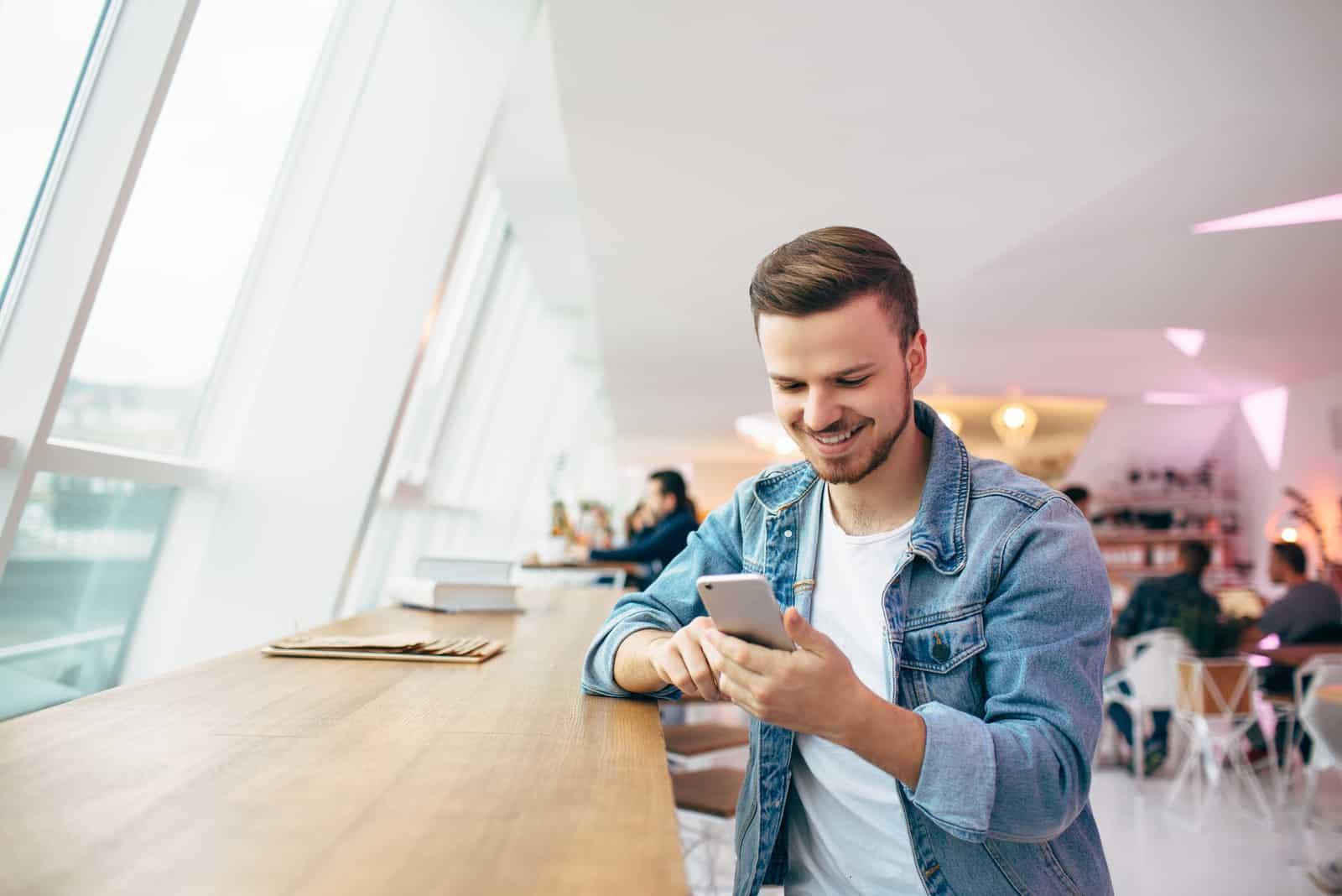 un homme souriant assis à une table et appuyant sur un téléphone