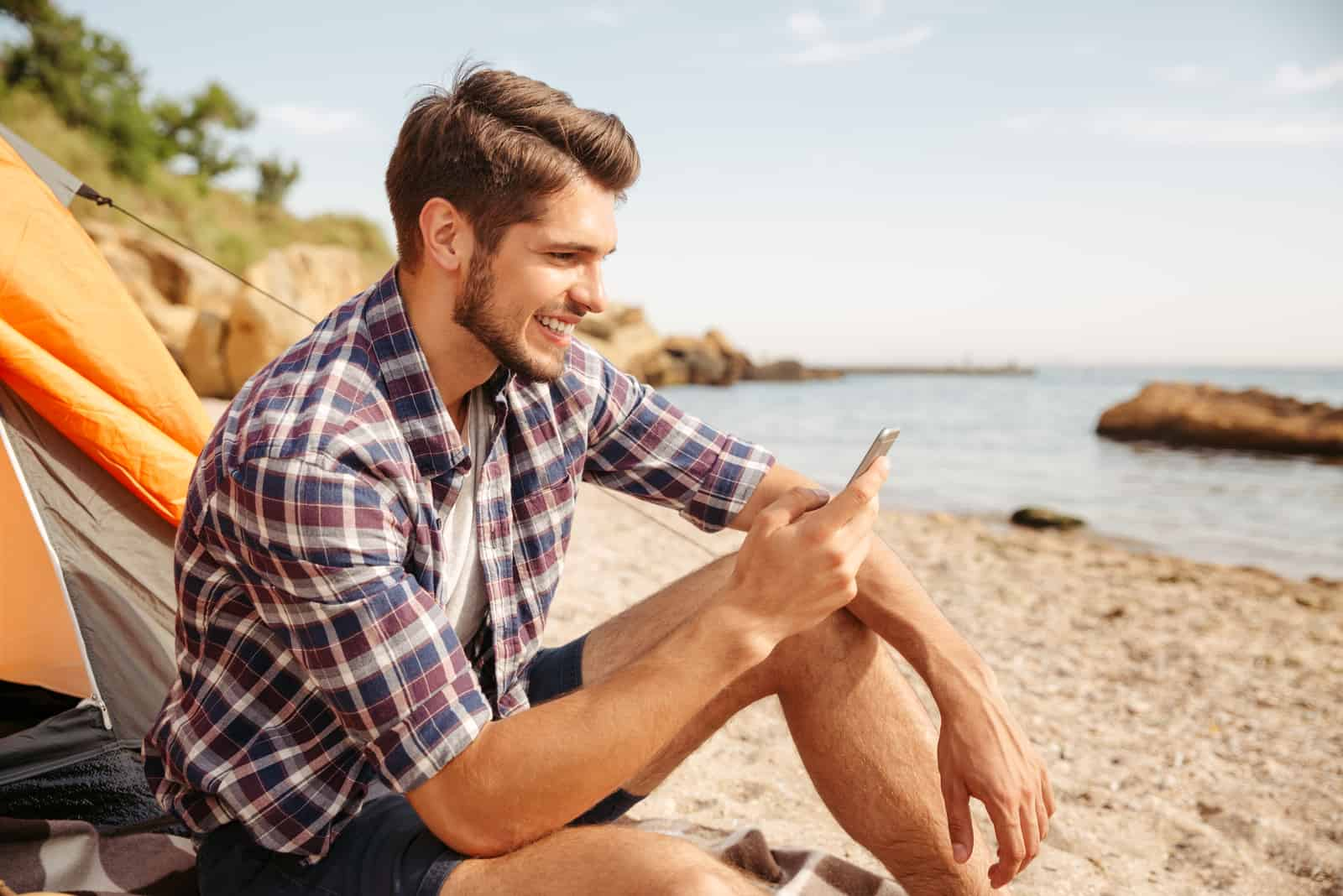 un homme souriant assis sur la plage et tapant au téléphone