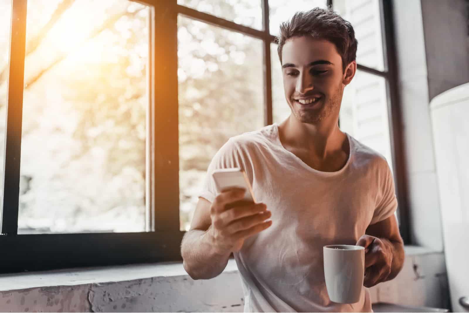 un homme souriant se tient avec une tasse à la main et des clés au téléphone