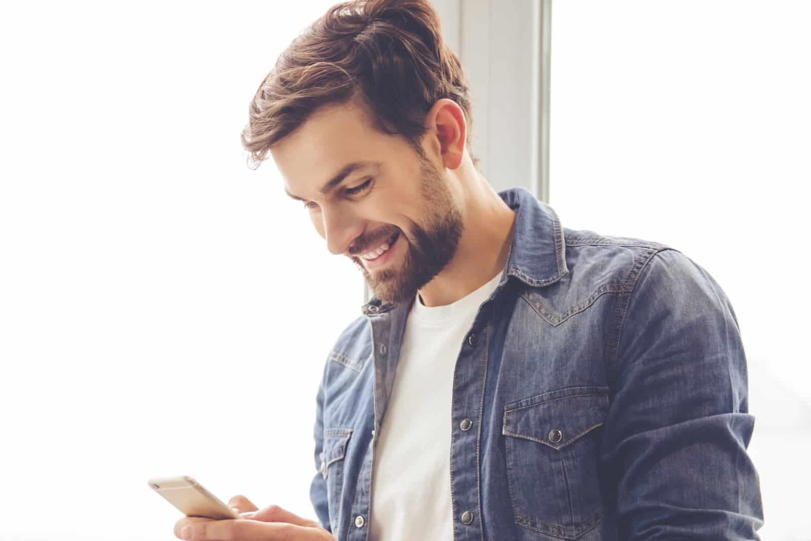 un homme souriant se tient près de la fenêtre et des boutons du téléphone