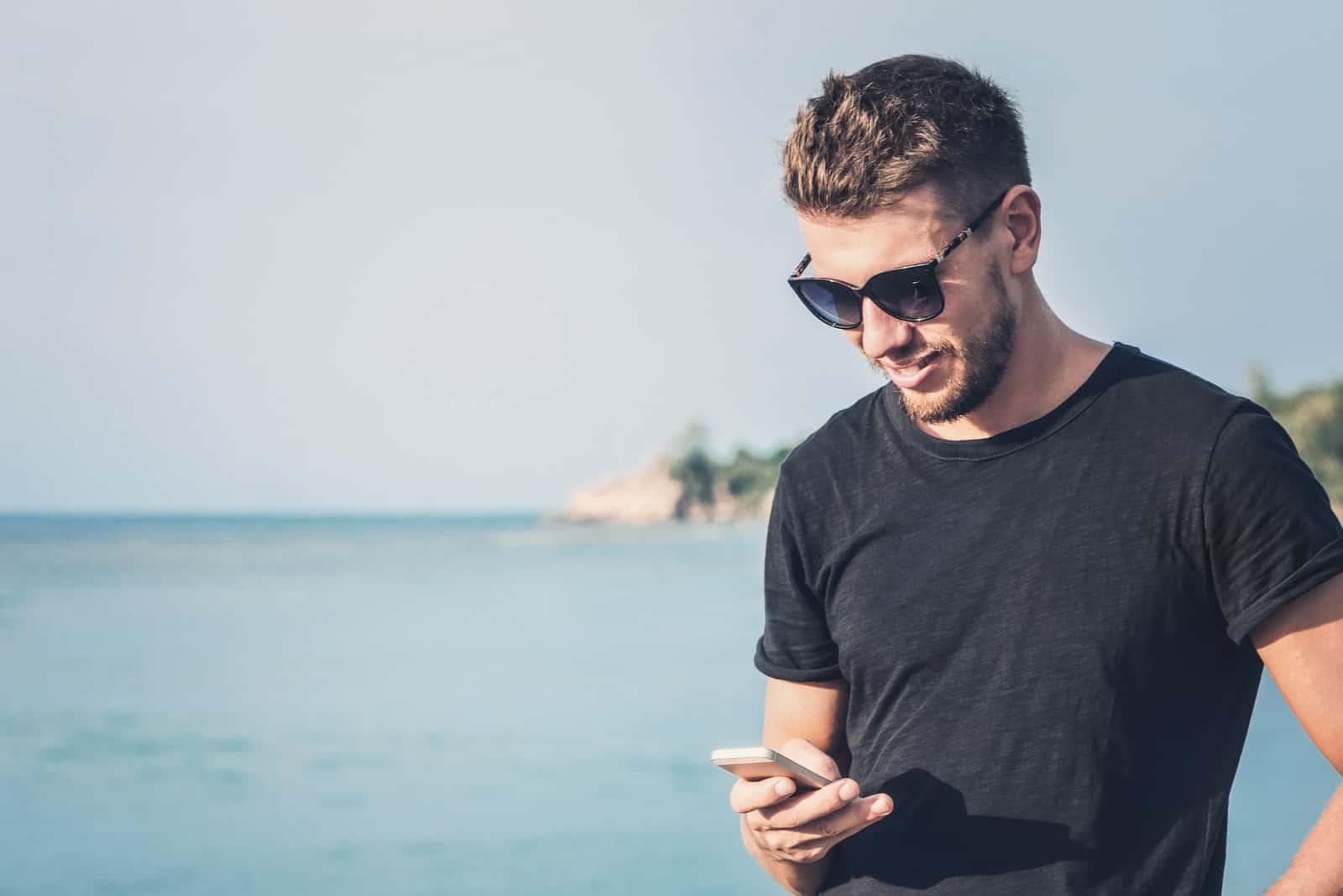 un homme souriant se tient près de la mer et des boutons du téléphone